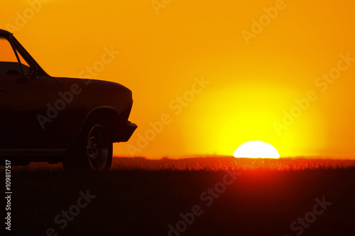 Obrazy na płótnie Canvas Retro red car standing on asphalt road at sunset