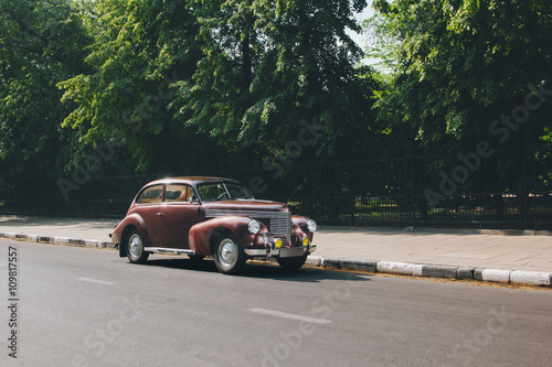 Poster Vintage voitures Retro car standing on road in the city