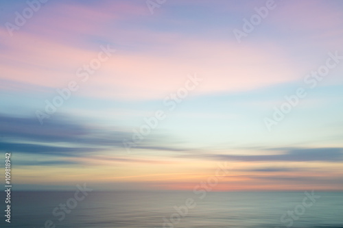 Blurred defocused sunset sky and ocean nature background.