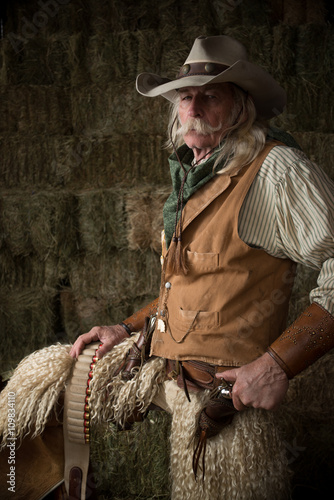 Old western cowboy with wooly chaps and pistols Poster