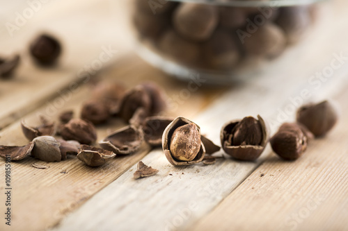 Deurstickers koffiebar Close-up of hazelnuts on wooden table. Some broken, shelled, some whole