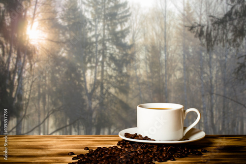 Poster Café en grains Coffee in cup on wooden table opposite blurred background. Colla