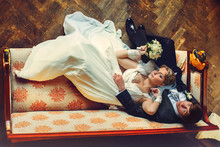 Bride Lays On Groom's Knees On The Old Red Sofa