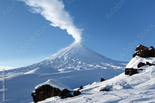 Spoed Foto op Canvas Vulkaan Beautiful winter volcanic landscape: view of eruption active Klyuchevskoy Volcano (Klyuchevskaya Sopka) in clear weather, sunny day. Russian Far East, Kamchatka, Klyuchevskaya Group of Volcanoes.