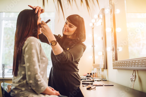 Fotografía  Professional expert,makeup artist prepares very beautiful,young,well-known,glamorous,stunning model for filming shooting for cover of fashion magazine VOGUE,does make-up,makes up lips,art,eyes,white