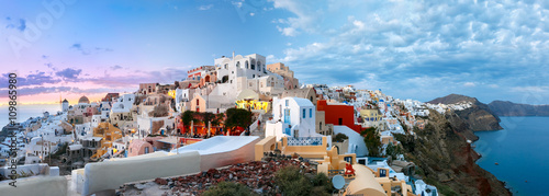 Papiers peints Europe Méditérranéenne Picturesque panorama, Old Town of Oia or Ia on the island Santorini, white houses, windmills and church with blue domes at sunset, Greece