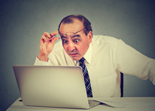Portrait Of A Shocked Man Reading Message On Computer In Office