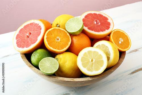 Fotografie, Obraz  frutta,agrumi interi e tagliati sfondo colorato