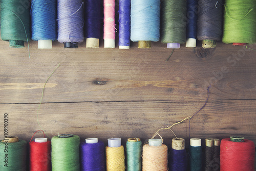 threads on wooden table Wallpaper Mural