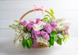 Lilac bouquet in basket with paper greeting card with hearts and