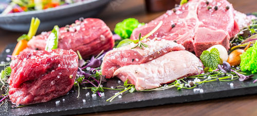 Staande foto Vlees Steak.Beef steak.Meat.Portioned meat.Raw fresh meat.Sirloin steak.T-Bone steak. Flank steak. Duck breast. Vegetable decoration. Portioned meat prepared for processing in a restaurant or hotel kitchen.