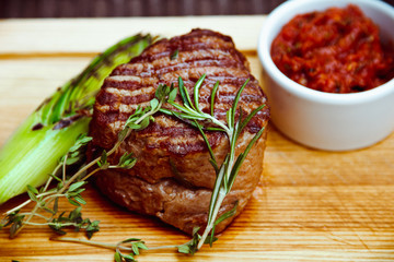 FototapetaBeautiful juicy well done steak with sauce on a wooden Board