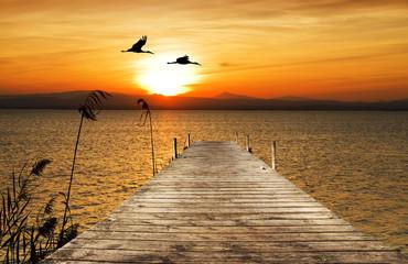 Fototapetapuesta de sol sobre el embarcadero del mar