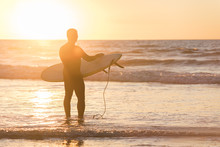 Silhouette Of A Surfer In Front Of Sun With Board During Sunset In San Diego, California, With Creative Flare