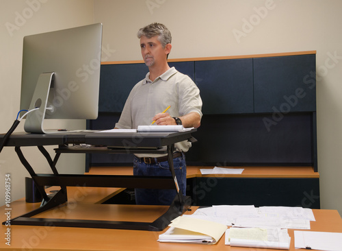Obraz na plátně A man is working at a standup desk in an office where he works because standing is healthier than sitting all day