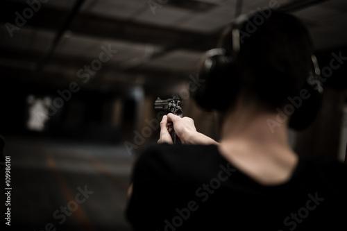 Pinturas sobre lienzo  Man aiming revolver at target in indoor firing range or shooting range