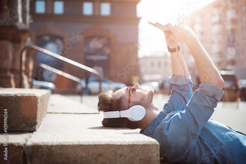 Valokuva  Positive guy lying on the footsteps
