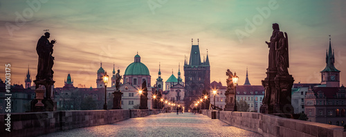 Prague Charles Bridge at sunrise, Prague, Czech Republic. Dramatic statues and medieval towers.