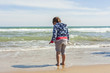 Rear view full shot girl walking to the shore of the beach in a