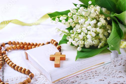 the first holy communion with rosary and flowers
