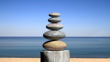 3D Rendering Of Balancing Zen Stones On The Beach, With Blue Sky And Peaceful Seascape.