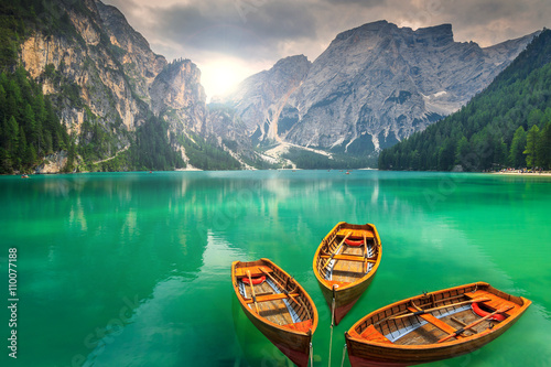 Stunning mountain lake with wooden boats in the Dolomites,Italy Wallpaper Mural
