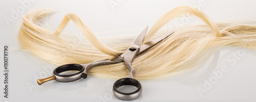 Fotografía  Hairdressing Scissors with a strand blond hair on a light background close-up