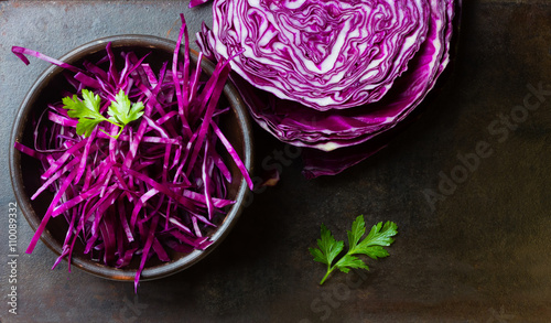 Leinwand Poster Shredded red cabbage in clay bowl. Background. Top view