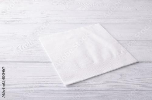 Fototapeta White napkin on a white wooden table. Top view obraz