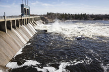 Horizontal Image Of A Large Hydro Dam With Water Churning Aggressively Over The Turbines In The Summer Time.