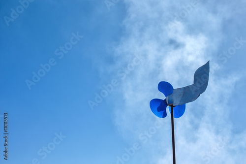 metal weather vane with pinwheel. homemade weathervane with a spinner and tail of the aircraft on background blue sky. copy space for your text