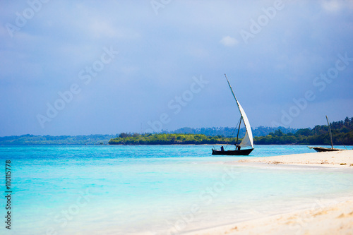 Poster Zanzibar Old wooden dhow on white beach in the Indian Ocean