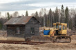 Yellow bulldozer in the sand near the wooden house in a forest