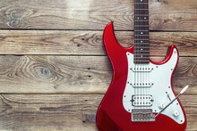 Red Electric Guitar On Grunge Wooden Planks Background. Place Fo