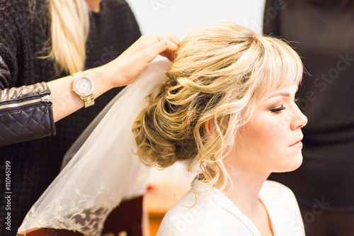 Fotografie, Obraz  Hair stylist makes the bride before a wedding
