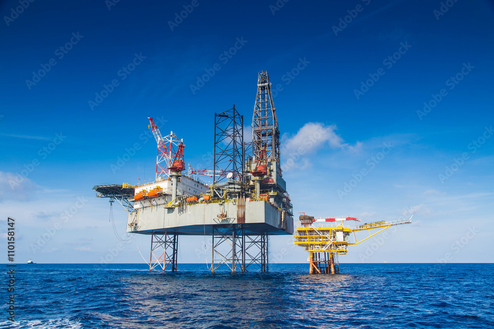 Fototapety, obrazy: Oil and gas drilling rig work over remote wellhead platform to completion oil and gas produce well by using drilling bit which made from carbide or diamond at head bit and drive by mud pressure