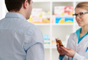 Male customer buying pills in drug store. Young female pharmacist consulting client, holding medicine bottle.