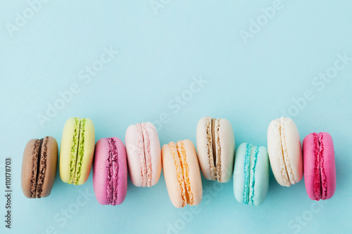 Fotografie, Obraz  Cake macaron or macaroon on turquoise background from above, colorful almond coo