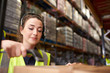 Woman uses barcode reader in a warehouse, head and shoulders