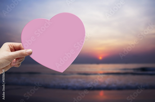 Fototapety, obrazy: Woman hand holding pink paper heart on the beach