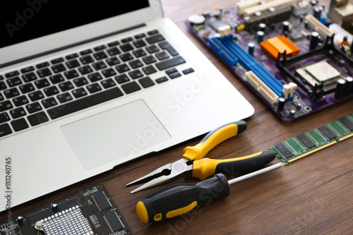 Fotografía  Laptop and Different electronic circuits, tools on wooden background