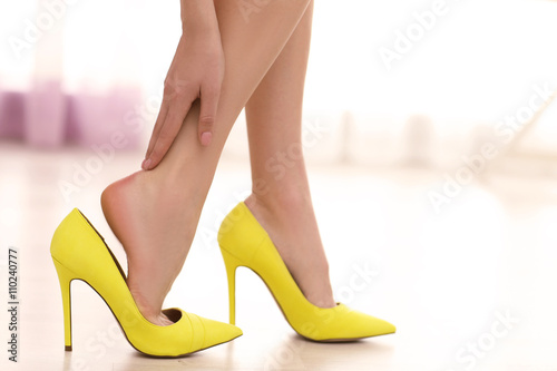 Fotografie, Obraz Woman taking off yellow high heels shoes.