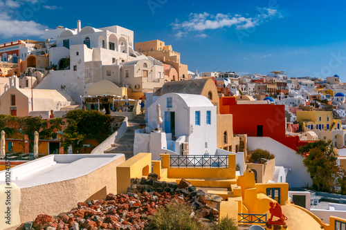 Poster de jardin Europe Méditérranéenne Picturesque view of white houses, windmills and church with blue domes in Oia or Ia, island Santorini, Greece