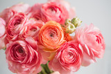 bunch of pale pink ranunculus persian buttercup  light background, wooden surface. glass vase