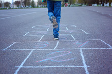 Kids Playing Hopscotch On Playground Outdoors.
