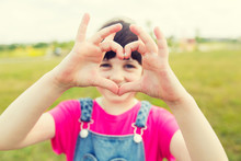 Happy Little Girl Making Heart Shape Gesture