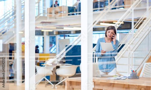 Businesswoman in open-plan office talking on phone
