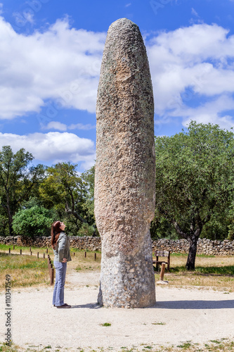 Fényképezés Woman looking at the Standing Stone / Menhir of Meada, the largest of the Iberian Peninsula