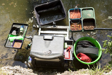 Fishing Competition. The Kit For A Professional Fisherman At A Fishing Competition Including A Comfortable Seat, Trays Of Live Worms, Gear To Fix The Line And A Fishing Net To Keep The Catch Alive