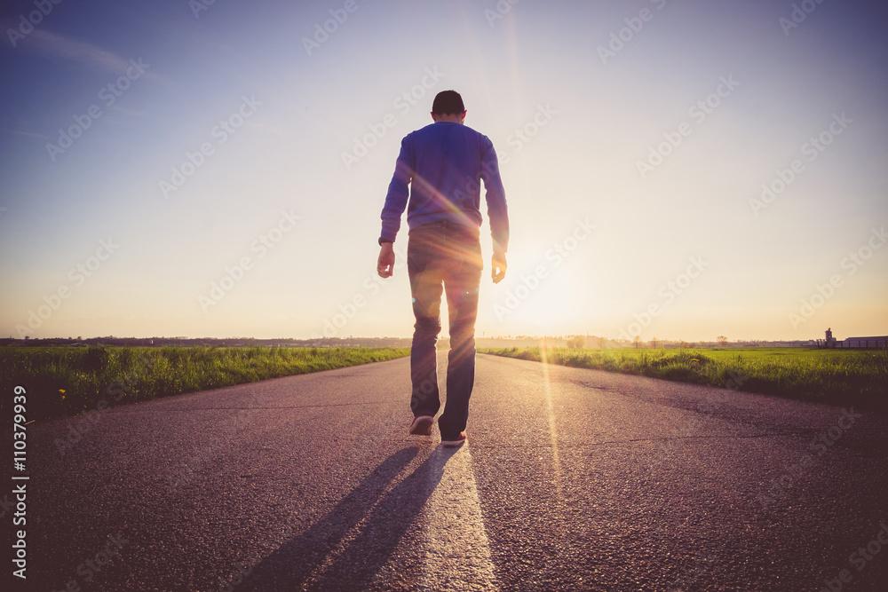 Fototapeta Man walking on the line on a paved road